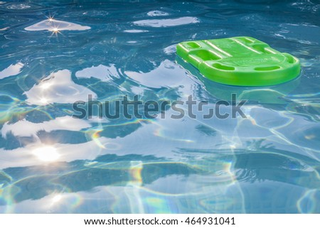 Green lifesaver floating in a swimming pool in summer time with sun reflection