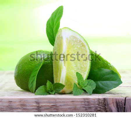 Green limes with leaves on wooden background
