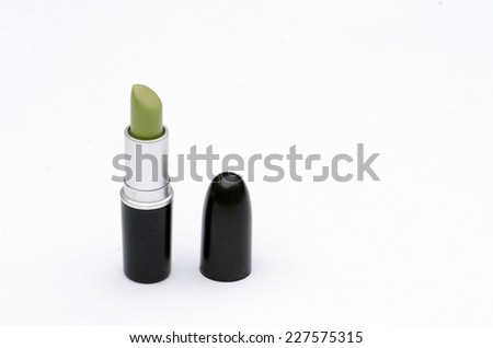green lipstick for mask's make up  with black and silver case in white background  - stock photo