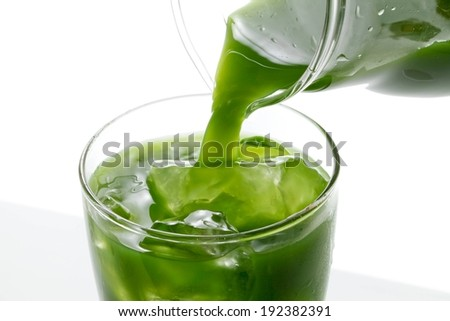 Green liquid being poured into a glass from a jug, ice in the glass - stock photo