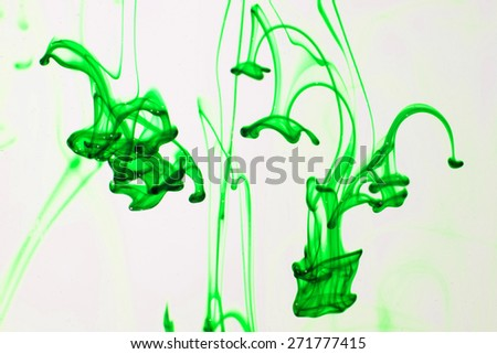 Green liquid ink  in water making abstract forms - stock photo