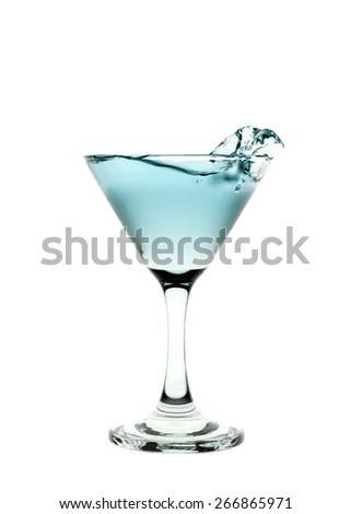 Green liquid splashing in a martini glass isolated on white background