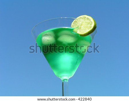 Green liquid with slice of lemon against clear blue sky