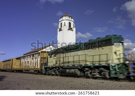 green locomotive shows motion as it passes a depot - stock photo