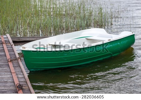 Green lonely boat on a lake  - stock photo