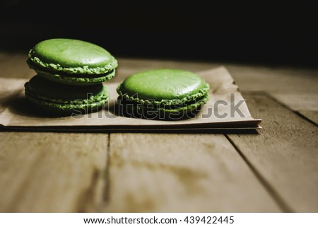 green macaroons with delicious taste on craft paper on wooden background