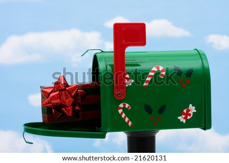 Green mailbox with a present inside and the flag up on a blue sky background, mailbox - stock photo
