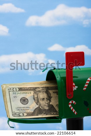 Green mailbox with twenty dollar bills on a blue sky background, mailbox - stock photo