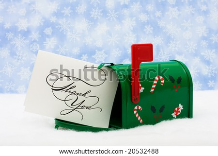 Green mailbox with white thank you card and the flag up sitting on snow with a snowflake background, mailbox - stock photo