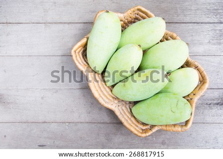 green mango in basket on wooden background - stock photo