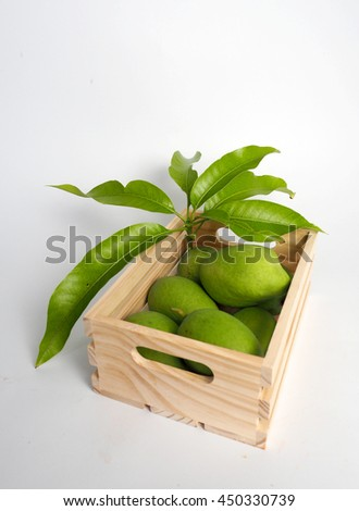 green mango in wooden box (white background)
