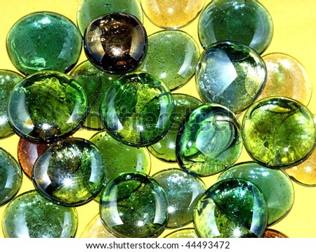 Green marbles on yellow background - stock photo