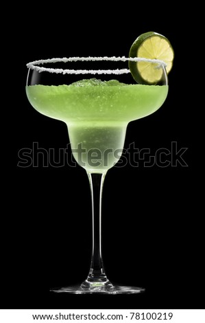 Green Margarita in front of a black background with fresh garnish - stock photo