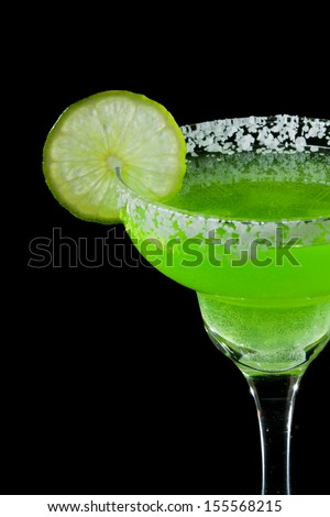 green margarita isolated on a black background served with a thick salt rim