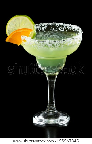 green margarita isolated on a black background served with a thick salt rim and a lime and orange on the rim
