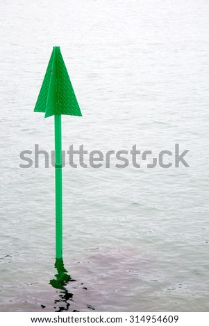 Green marker post in sea warning of submerged object - stock photo