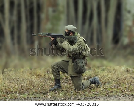Green Masked airsoft player, who plays for Russian side of the army, old time scenery, blurred blackground - stock photo
