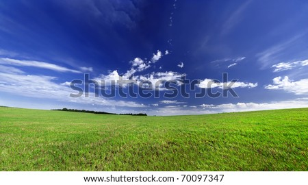 green meadow and a deep blue sky - stock photo