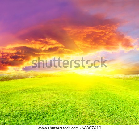 Green meadow and bright sky during sundown.