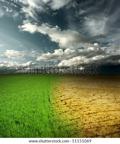 Green meadow and cracked desert land under storm clouds - stock photo