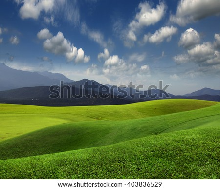 Green meadow and mountains on the horizon - stock photo