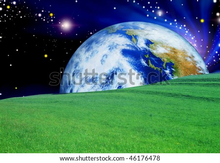 green meadow with the planet on the horizon - stock photo