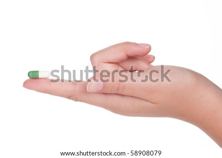 green medical capsule in a female hand, isolated