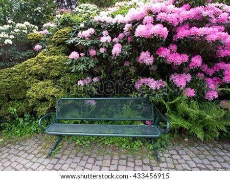 Green metal bench on sidewalk in beautiful floral park - stock photo