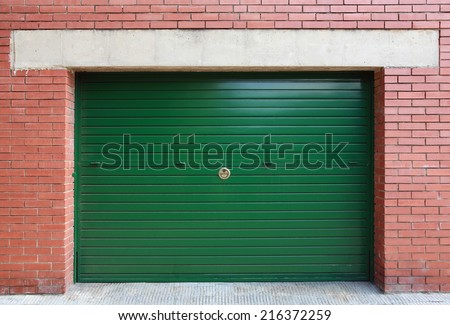 Green metal garage gate in red brick wall, background photo texture - stock photo