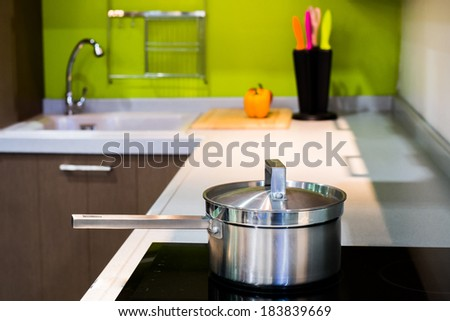 green modern kitchen  and stainless steel pot on induction electric hob - stock photo
