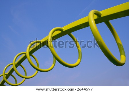Green Monkey Exercise Hoops from a playground against blue sky - stock photo