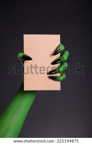 Green monster hand with black nails holding blank piece of cardboard, Halloween theme   - stock photo