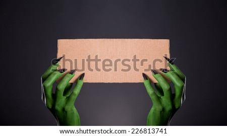 Green monster hands with black nails holding empty piece of cardboard, Halloween theme   - stock photo
