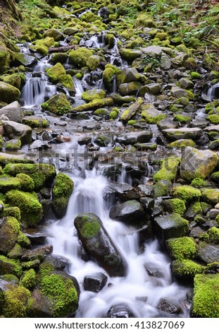Green moss covered stones in waterfalls - stock photo