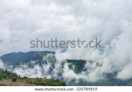Green mountain hills among clouds and lonely house - stock photo