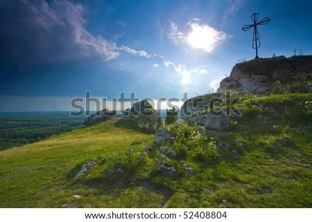 green mountain peak with cross and dramatic light - stock photo