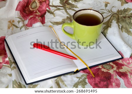 Green mug with tea or coffee in bed with bedding with floral print diary with a pencil or pen note thoughts dreams - stock photo