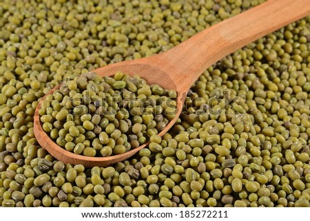 Green mung beans in a wooden spoon