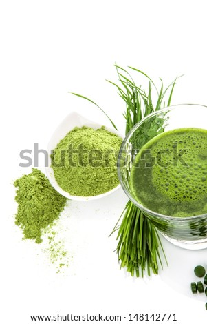 Green natural superfood. Detox. Healthy living. Wheatgrass, chlorella spirulina. Ground powder, pills, green juice and blades. - stock photo