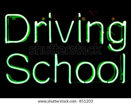Green neon sign advertising driving school