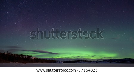 Green northern lights (aurora borealis) substorm, a few clouds and lots of stars on night sky above snowy hills. - stock photo