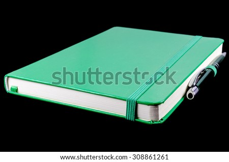 Green notebook isolated on black - stock photo