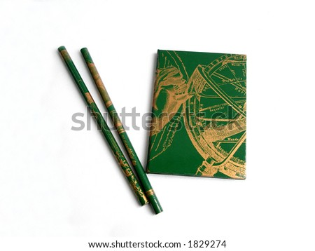 green notebook with two green pencils on a white background - stock photo