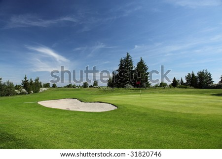 green of a beautiful golf course surrounded with bunkers with dramatic summer sky