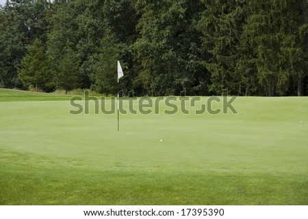 green of a beautiful golf course with dramatic summer sky - stock photo