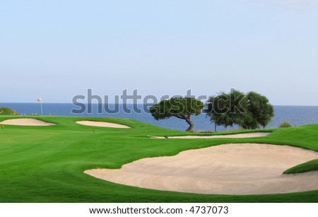 Green of a golf field with a beautiful view to the sea - stock photo
