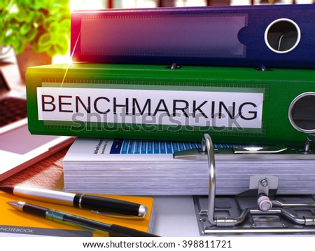 Green Office Folder with Inscription Benchmarking on Office Desktop with Office Supplies and Modern Laptop. Benchmarking Business Concept on Blurred Background. Benchmarking - Toned Image. 3D. - stock photo