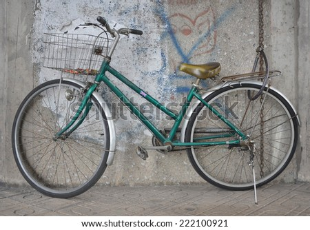 green old bicycle and the old wall - stock photo