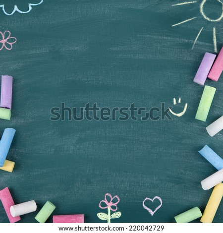 Green old empty chalkboard for copy space with colorful pieces of chalk - stock photo