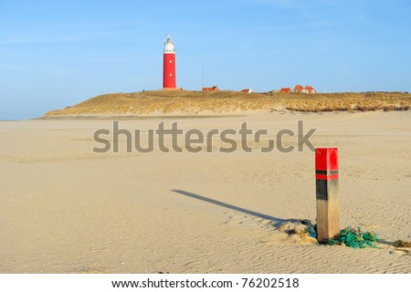 Green old fishing net and pole at the beach with lighthouse - stock photo